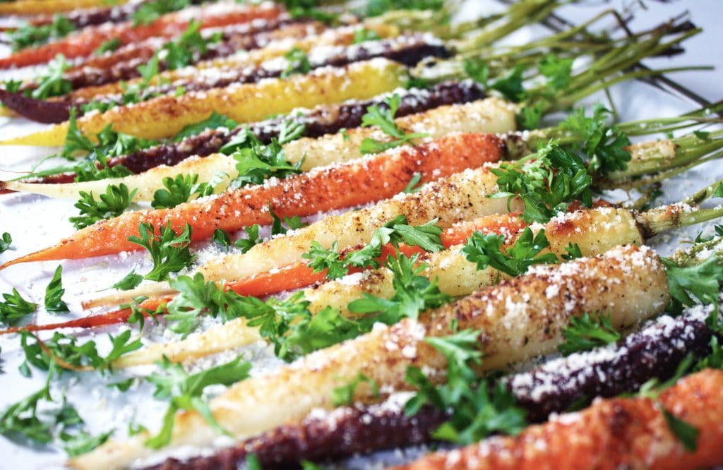 side angle shot of rainbow carrots garnished with parsley and parmesan cheese