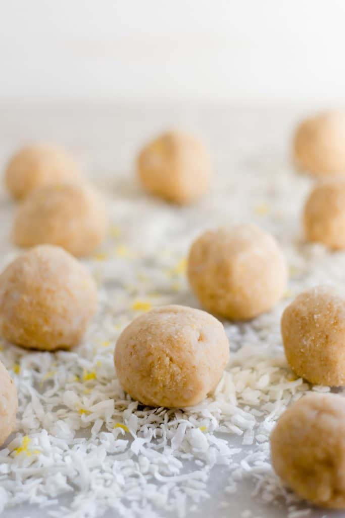 ten lemon bar fat bombs that have been rolled into bite-sized balls