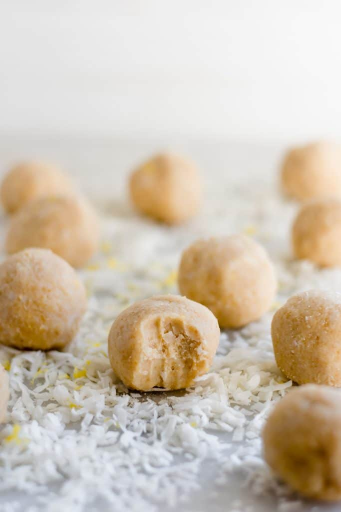 ten lemon bar fat bombs with one having a tiny bite mark on a bed of desiccated coconut