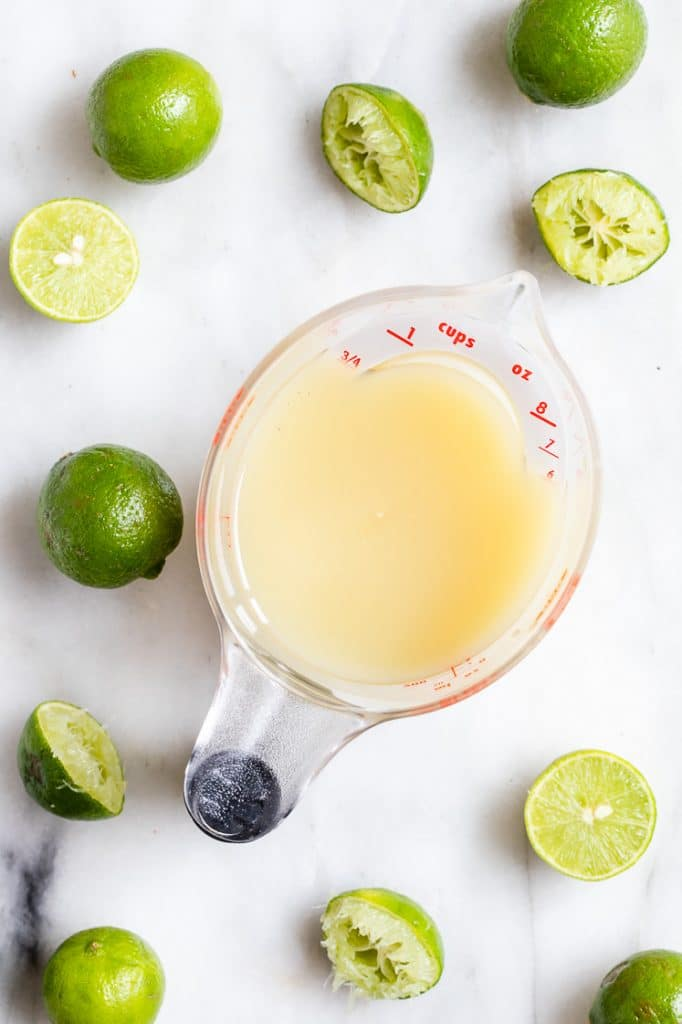key lime juice in a measuring cup beside halved limes