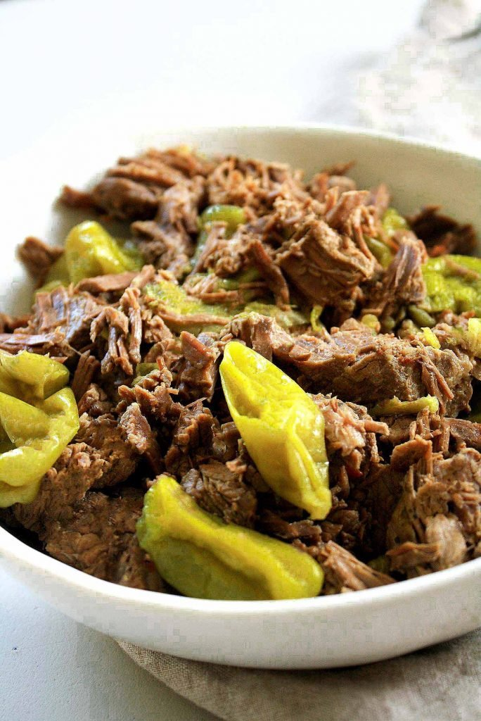 Low-FODMAP Pressure Cooker Italian Beef in a white ceramic bowl with lots of peperoncini