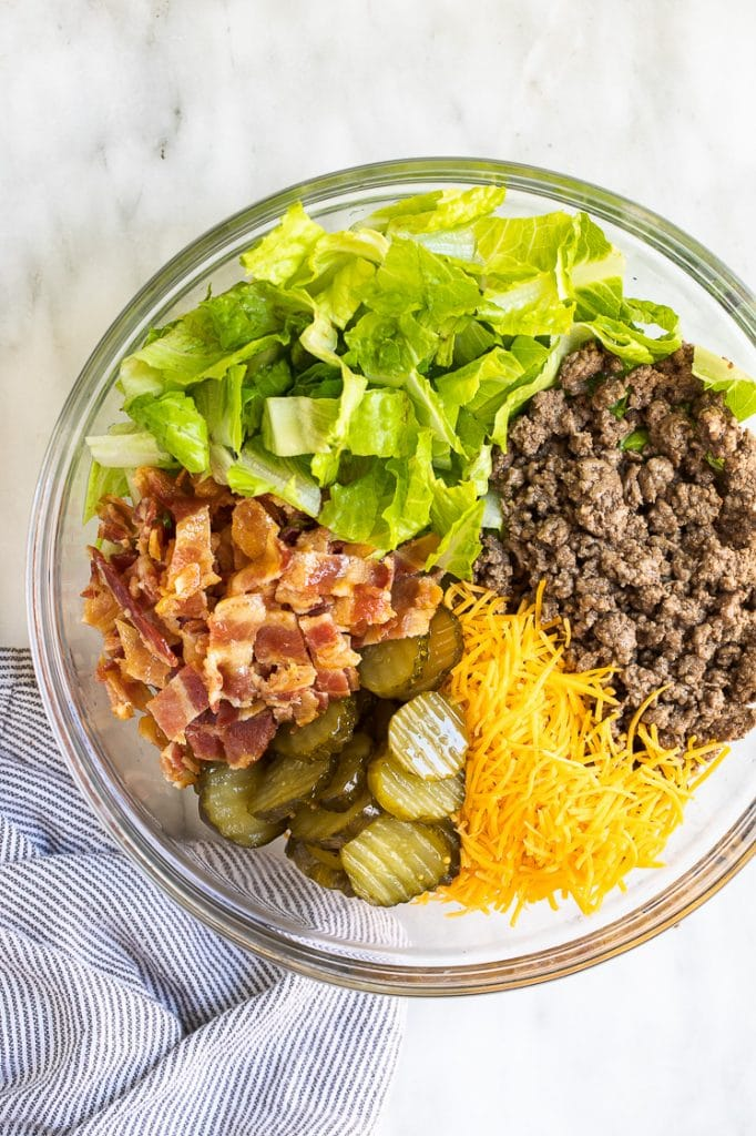 Keto Bacon Cheeseburger Salad ingredients in a glass mixing bowl atop a marble kitchen counter
