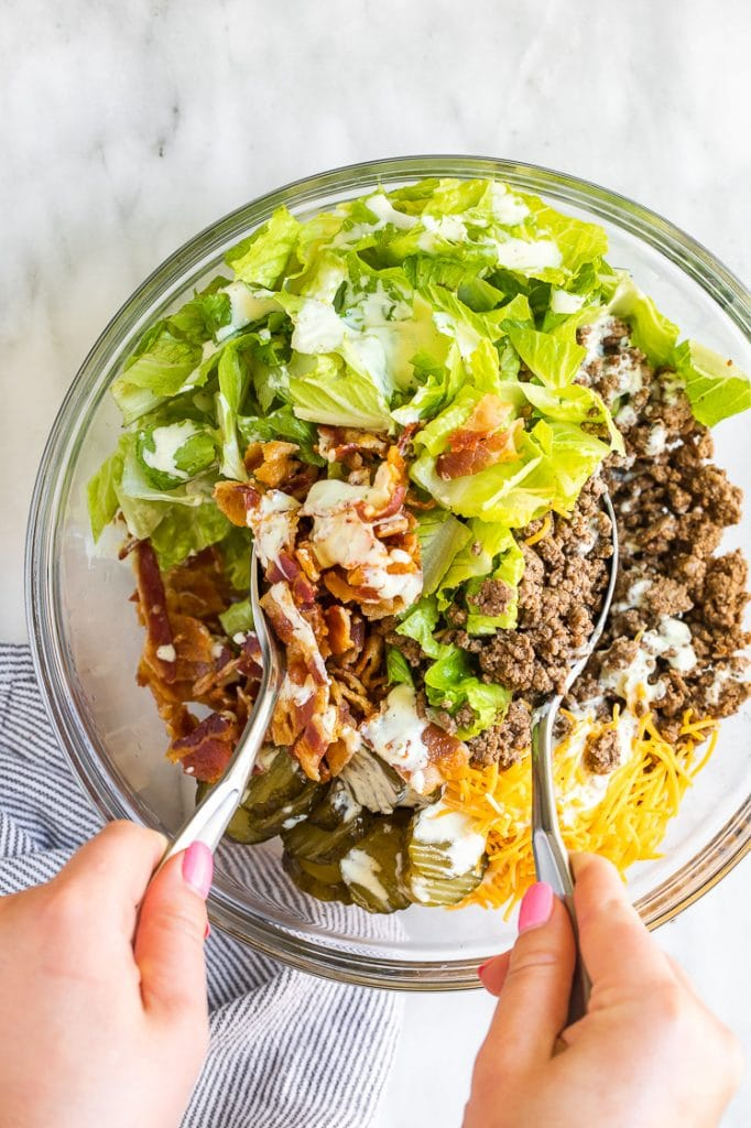 Keto Bacon Cheeseburger Salad ingredients mixed together using salad spoons in a glass mixing bowl atop a marble kitchen counter