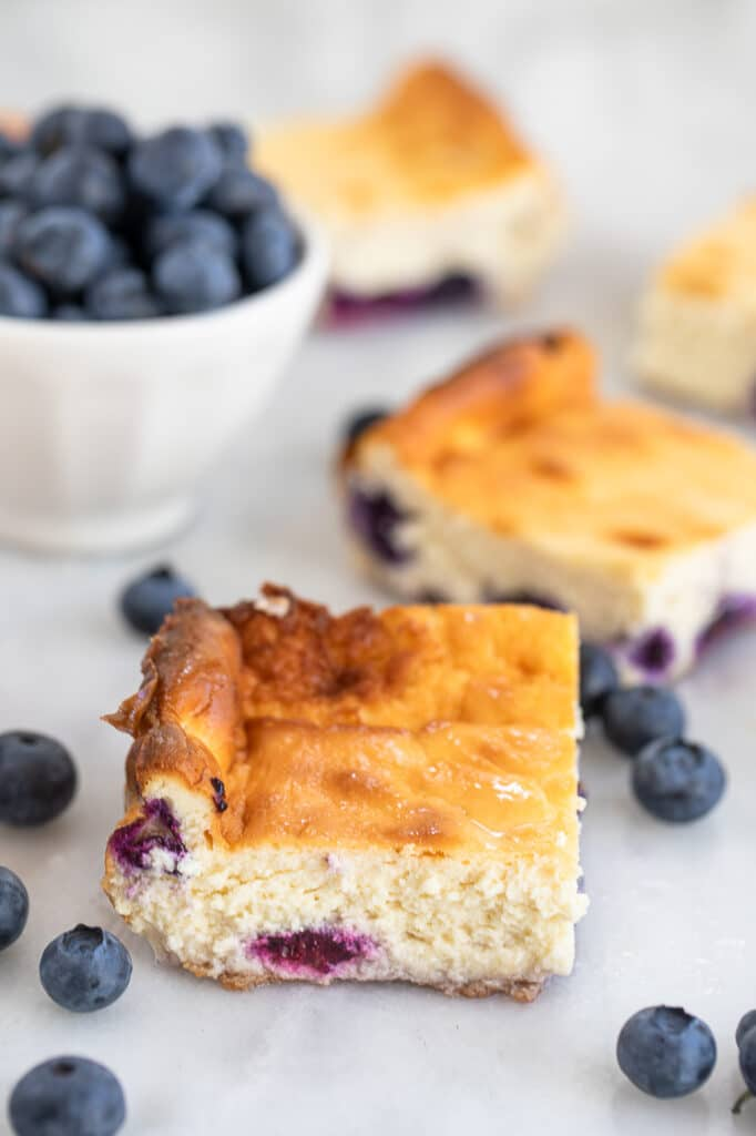 deliciously creamy cheesecake bars with blueberries atop a marble kitchen counter
