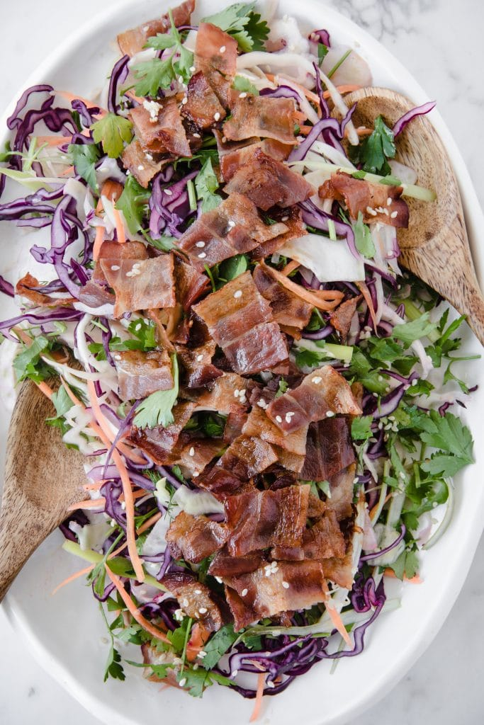 overhead shot of a keto bacon salad atop a marble kitchen counter with a wooden serving spoon