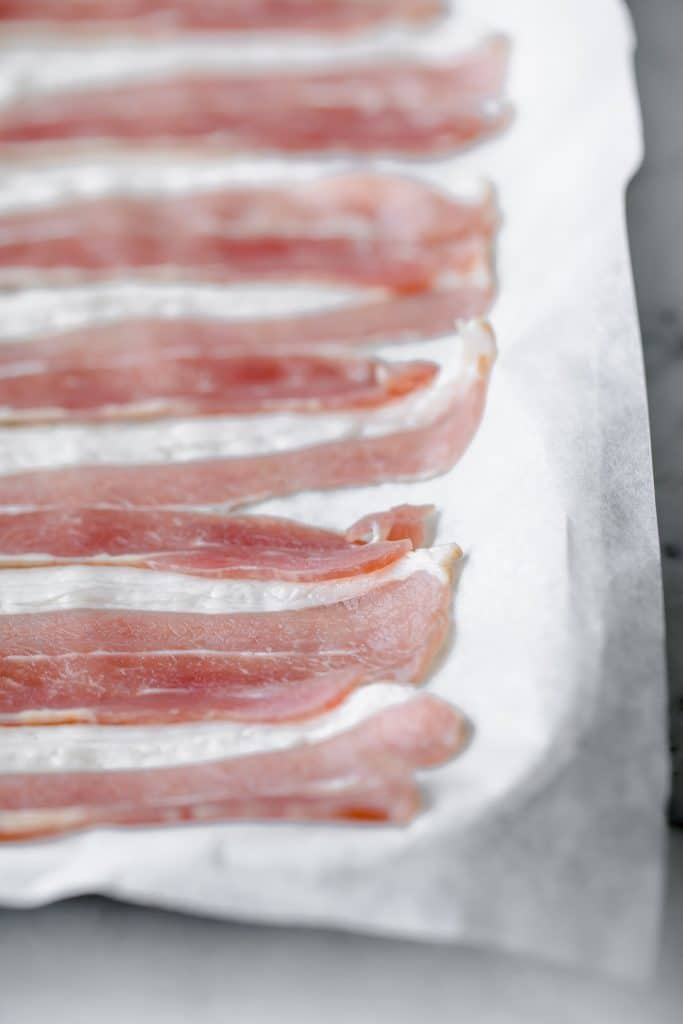 uncooked bacon strips aligned on a baking tray lined with parchment paper
