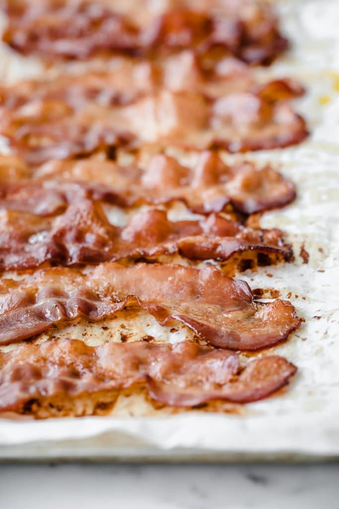 baked bacon strips aligned on a baking tray lined with parchment paper