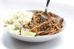 paleo low carb carnitas with cauliflower rice and a lime wedge