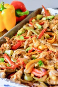 sheet pan fajitas beside yellow and red bell peppers