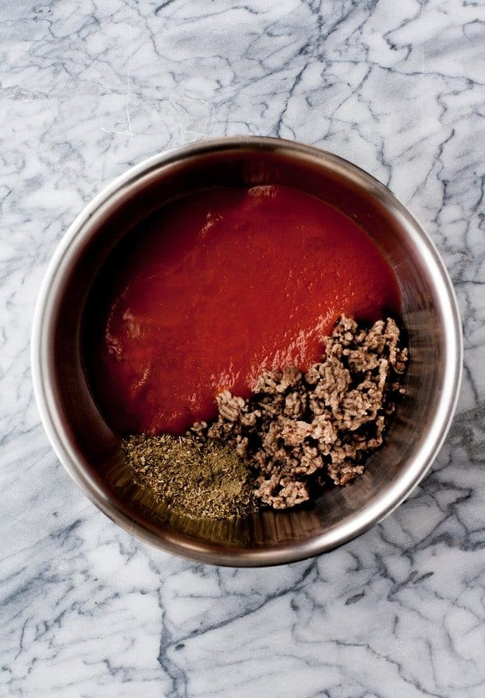 tomato-sauce-spices-and-beef-in-stainless-steel-bowl-on-marble-board