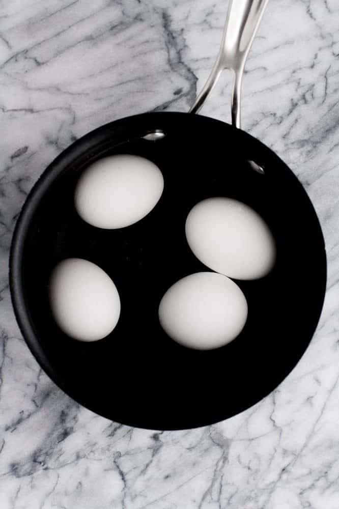 4 eggs in a small pot atop a marble kitchen counter