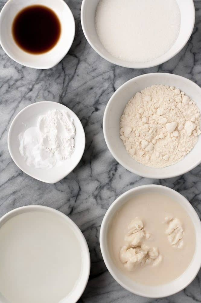 coconut oil, coconut butter, golden monk fruit sweetener, coconut flour, vanilla extract, cream of tartar, and baking soda assembled atop a marble kitchen counter