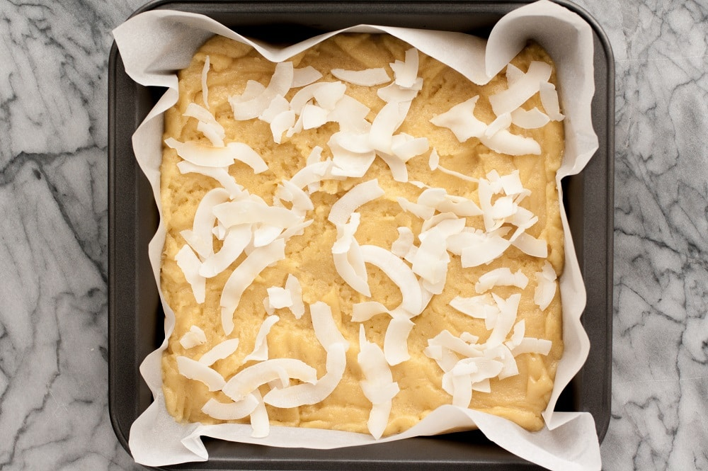 low carb coconut blondies batter in a baking tray lined with parchment paper topped with coconut flakes atop a marble kitchen counter