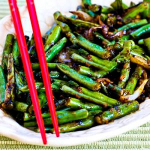 Keto Side Dish Recipes - garlic green beans stirfry eaten with chopsticks