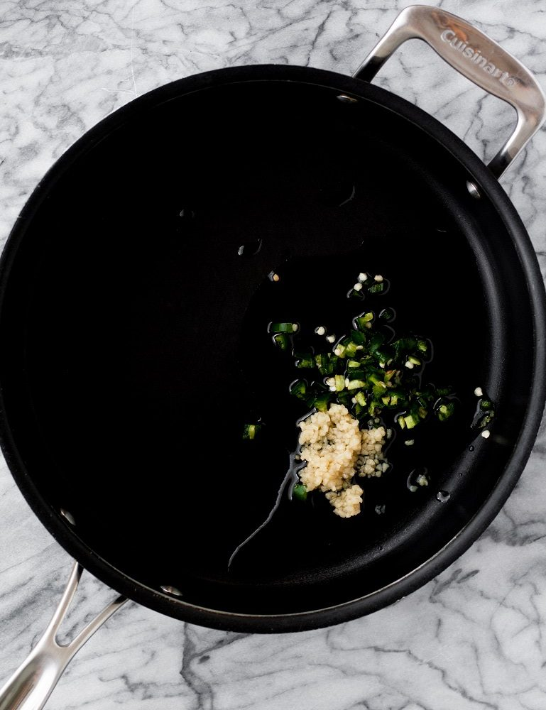 chopped-jalapenos-and-garlic-in-black-pan-on-marble-board