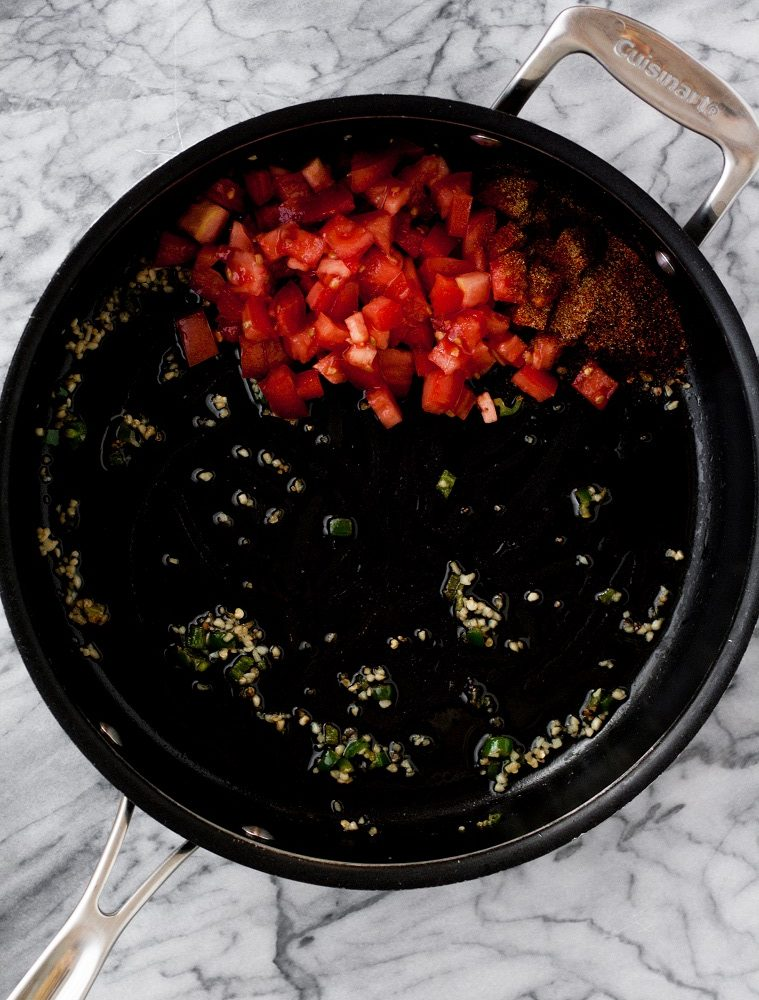 chopped-jalapenos-and-garlic-and-tomatoes-and-spices-in-black-pan-on-marble-board