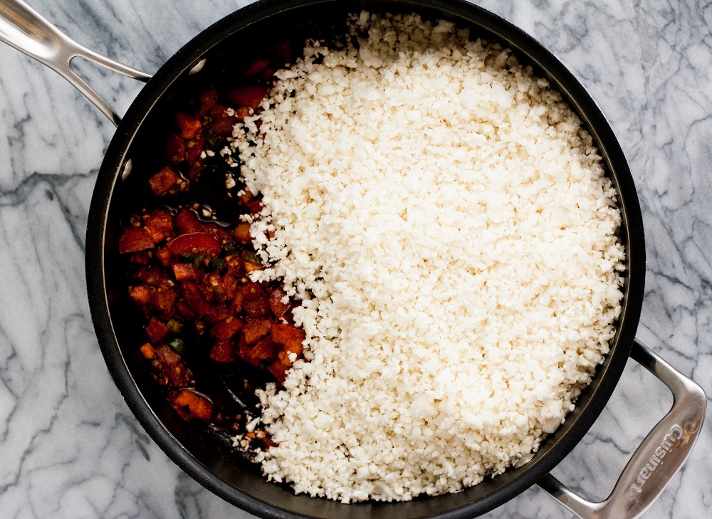 chopped-jalapenos-and-garlic-and-tomatoes-and-spices-and-cauliflower-rice-in-black-pan-on-marble-board