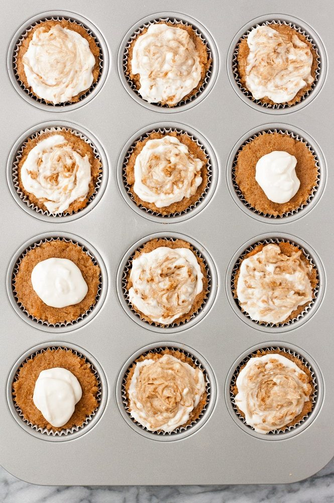 overhead shot of batter and cream cheese filling being swirled into pumpkin muffins in muffin tin