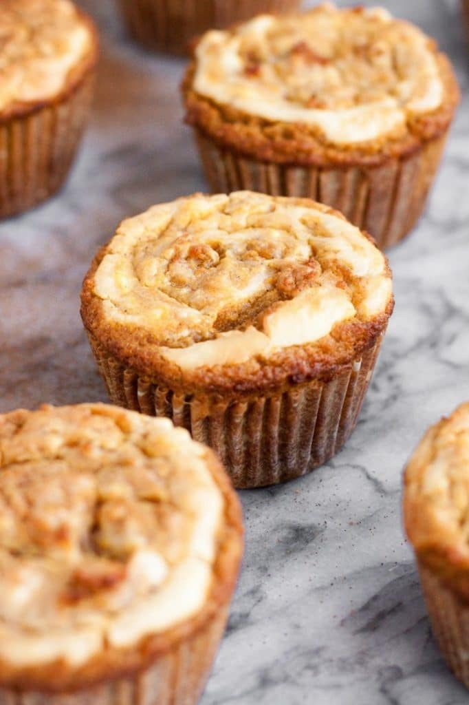 side angle shot of baked cream cheese pumpkin muffins on marble countertop