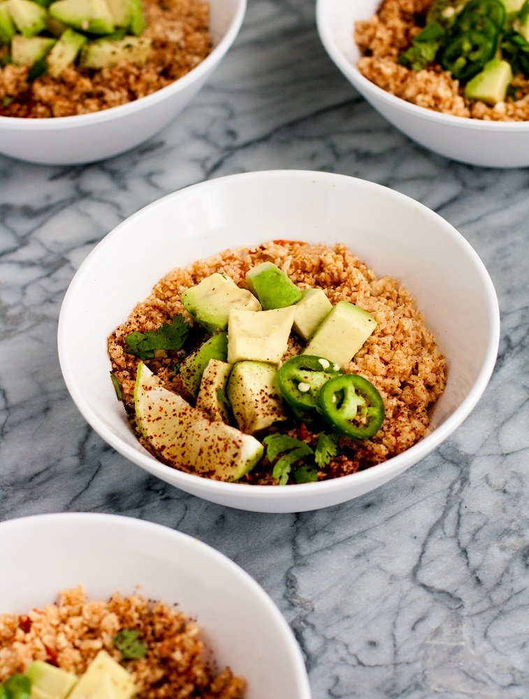 side-view-mexican-cauliflower-rice-in-white-bowls-on-marble-board
