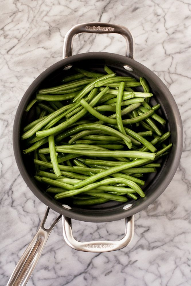 green beans in a steamer basket in a pot atop a marble kitchen counter