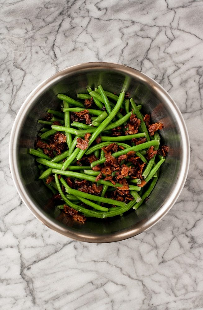 steamed green beans and crumbled bacon in a stainless steel mixing bowl atop a marble kitchen counter