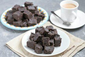 Heavenly Cream Cheese Dark Chocolate Keto Fudge on a plates beside a cup of coffee