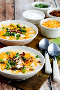 instant pot low carb loaded cauliflower soup in bowls beside spoons and garnish options