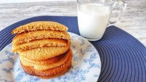 keto pumpkin cookies stacked on a ceramic saucer beside a glass cup of milk