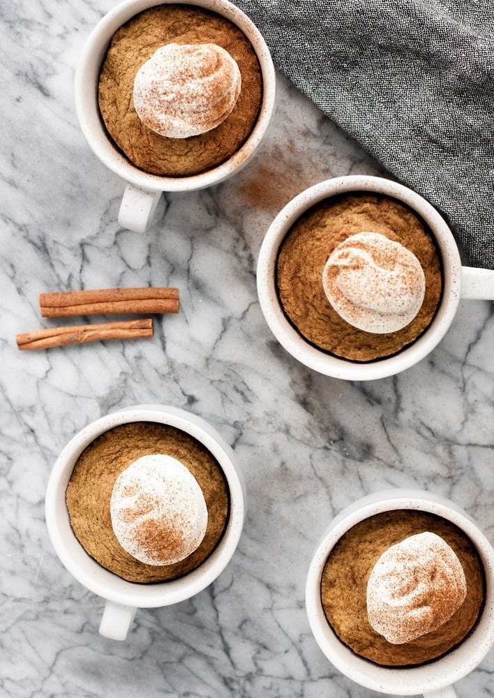 4 mugs of keto pumpkin pie mug cakes with whipped cream sprinkled with cinammon