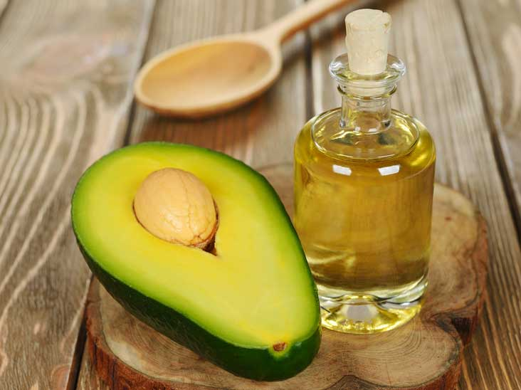 halved avocado beside a bottle of avocado cooking oil and a wooden spoon in the background