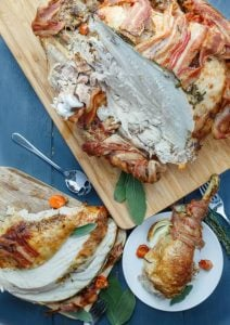 bacon wrapped whole turkey with herb butter served on a chopping board and plates