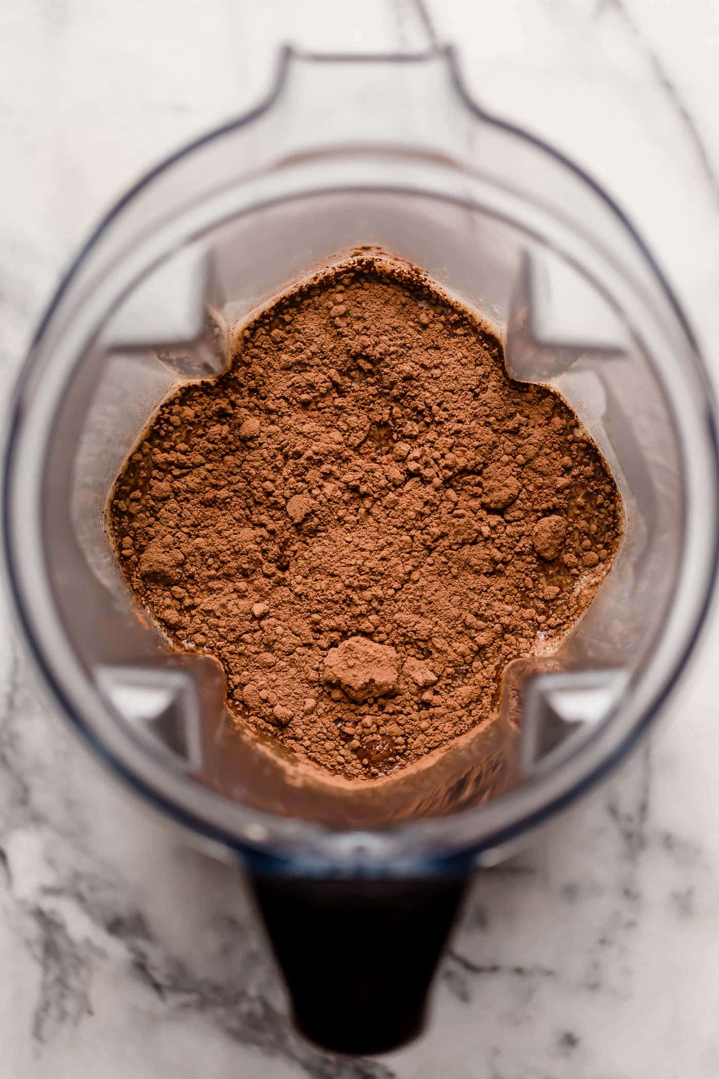 overhead shot of hot coffee with heavy cream and unsweetened cocoa powder
