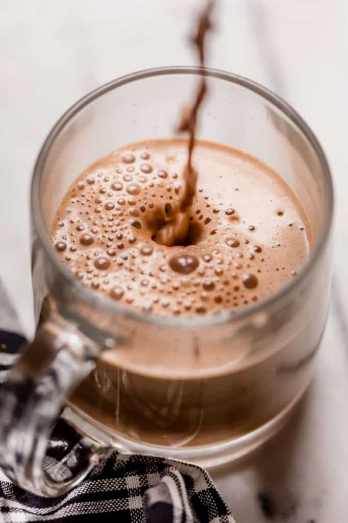 a serving of bulletproof peppermint mocha poured in a clear glass mug on top of a marble counter