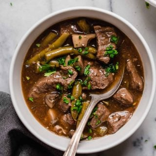 hero shot of instant pot beef stew in a ceramic bowl with a spoon