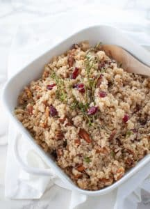 Cranberry Pecan Cauliflower Rice Stuffing in a square ceramic deep dish with a wooden spoon