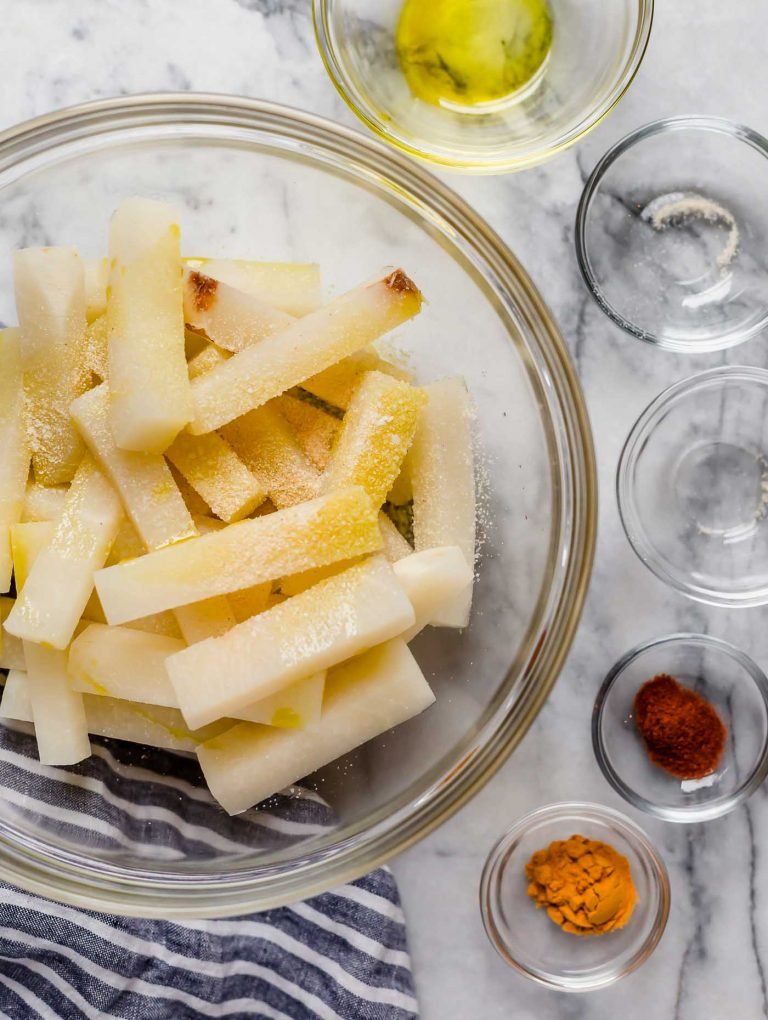 jicama fries in a large mixing bowl along with smaller bowls of spices onion powder poured in