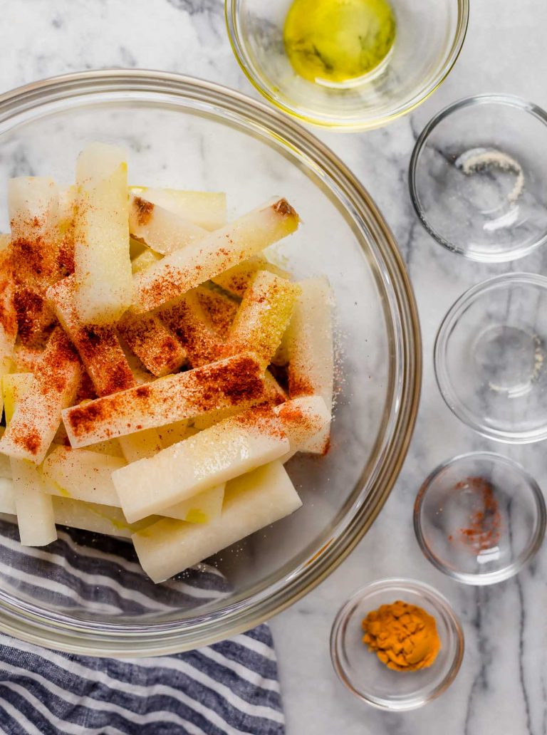jicama fries in a large mixing bowl along with paprika and other spices poured in