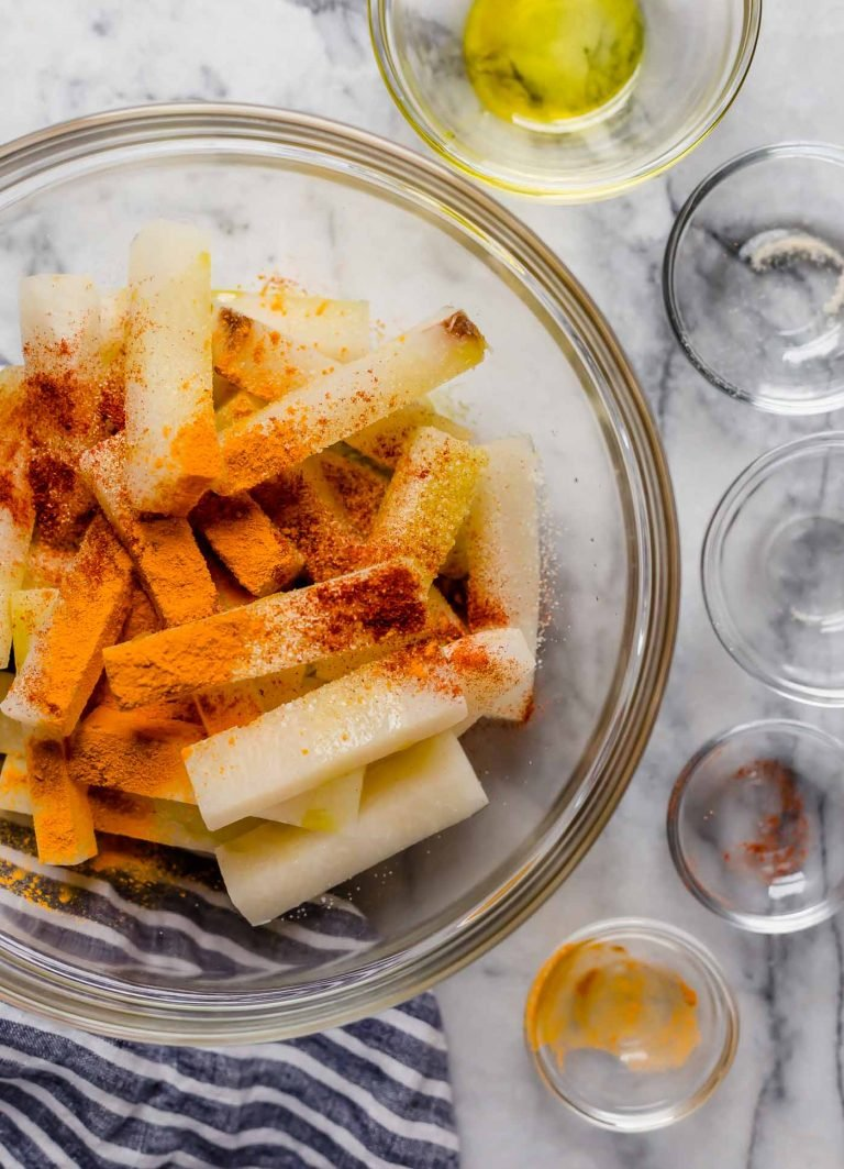 jicama fries in a large bowl with spices poured in