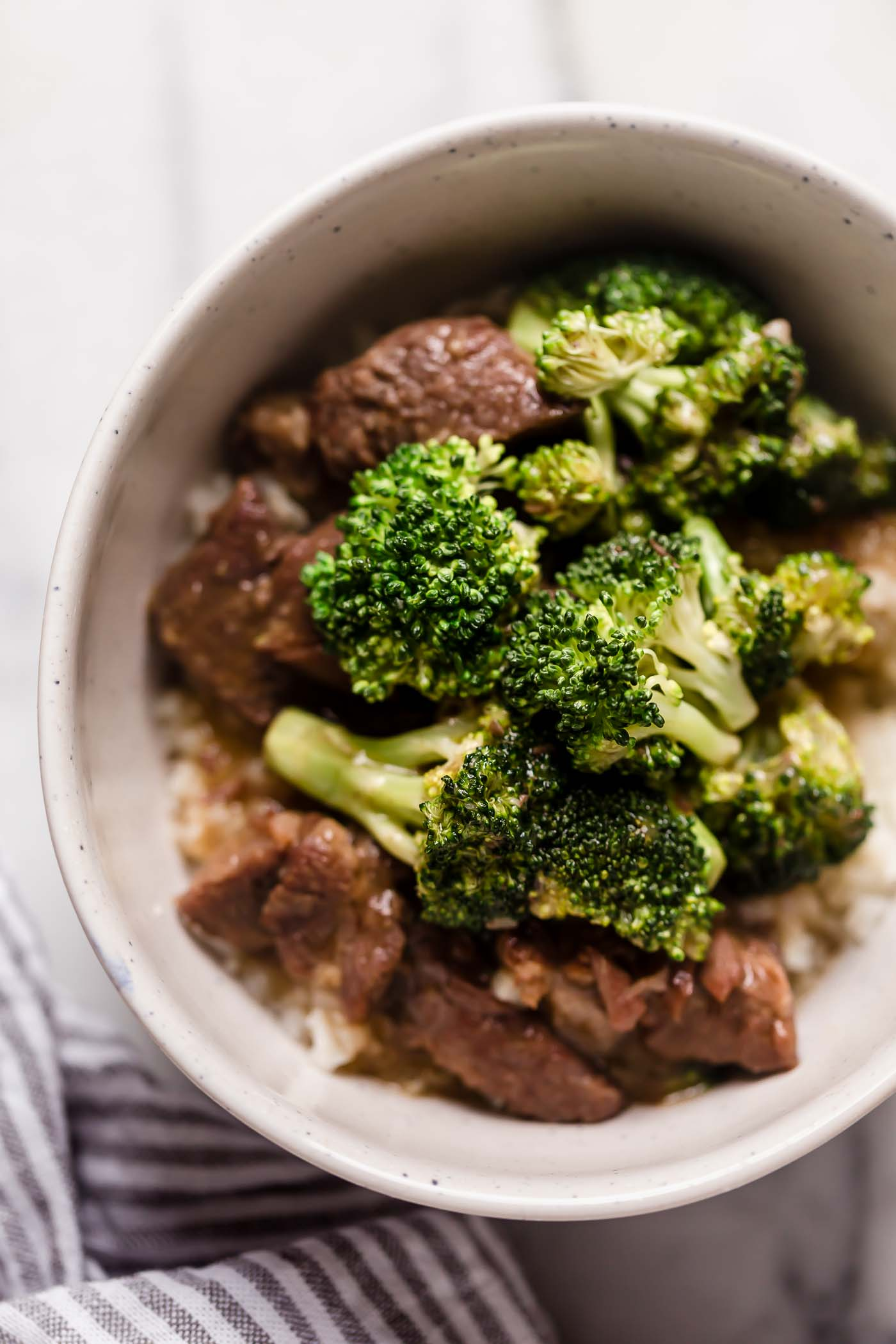 Instant Pot Beef Broccoli with Rice in a ceramic bowl on top of a marble counter