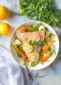 instant pot lemon garlic salmon on a plate with veggies beside parsley and lemons