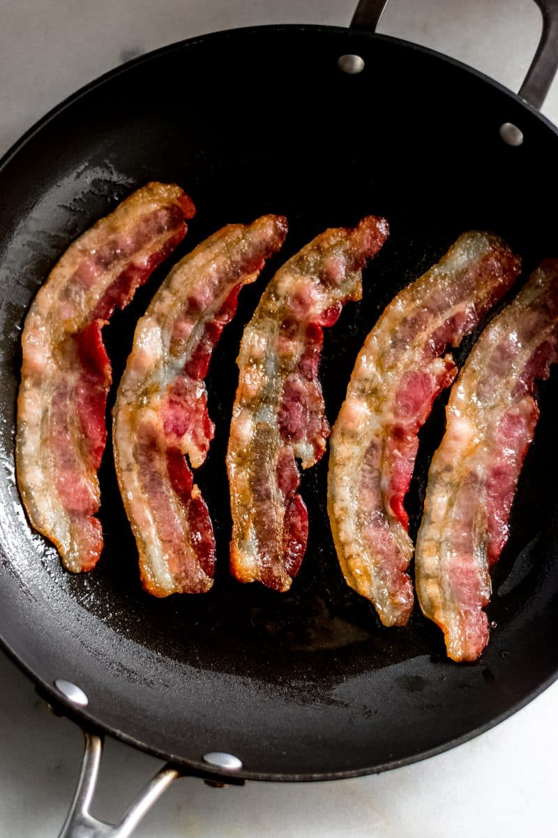 Overhead shot of bacon in skillet on marble board