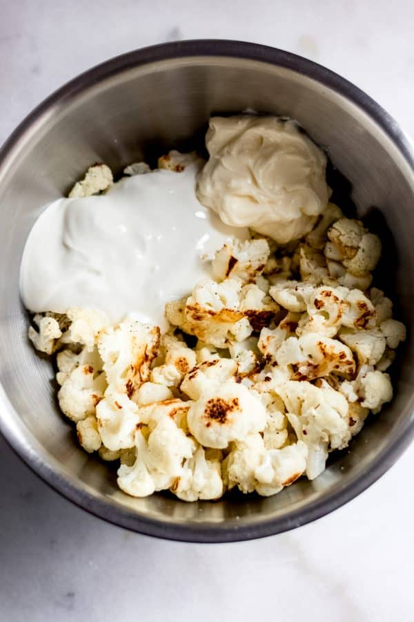 Overhead shot of stainless steel mixing bowl with unmixed cooked cauliflower, sour cream, and mayo