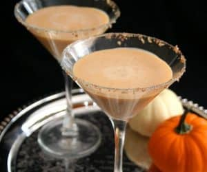 2 servings of pumpkin martinis on a silver platter beside pumpkin decor