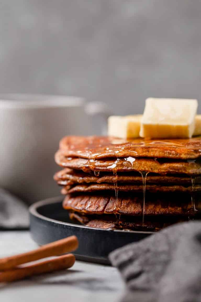 Side angle shot of flourless pumpkin spice pancakes with lakanto maple-flavored syrup and knobs of butter