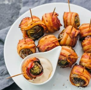 a plate of bacon-wrapped brussel sprouts and dip