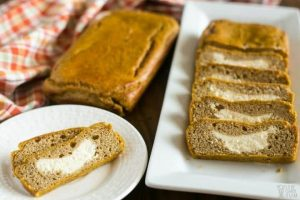 a loaf and some slices of cream cheese pumpkin bread on a rectangular plate