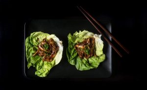general tso's instant pot shredded chicken on lettuce leaves beside chopsticks