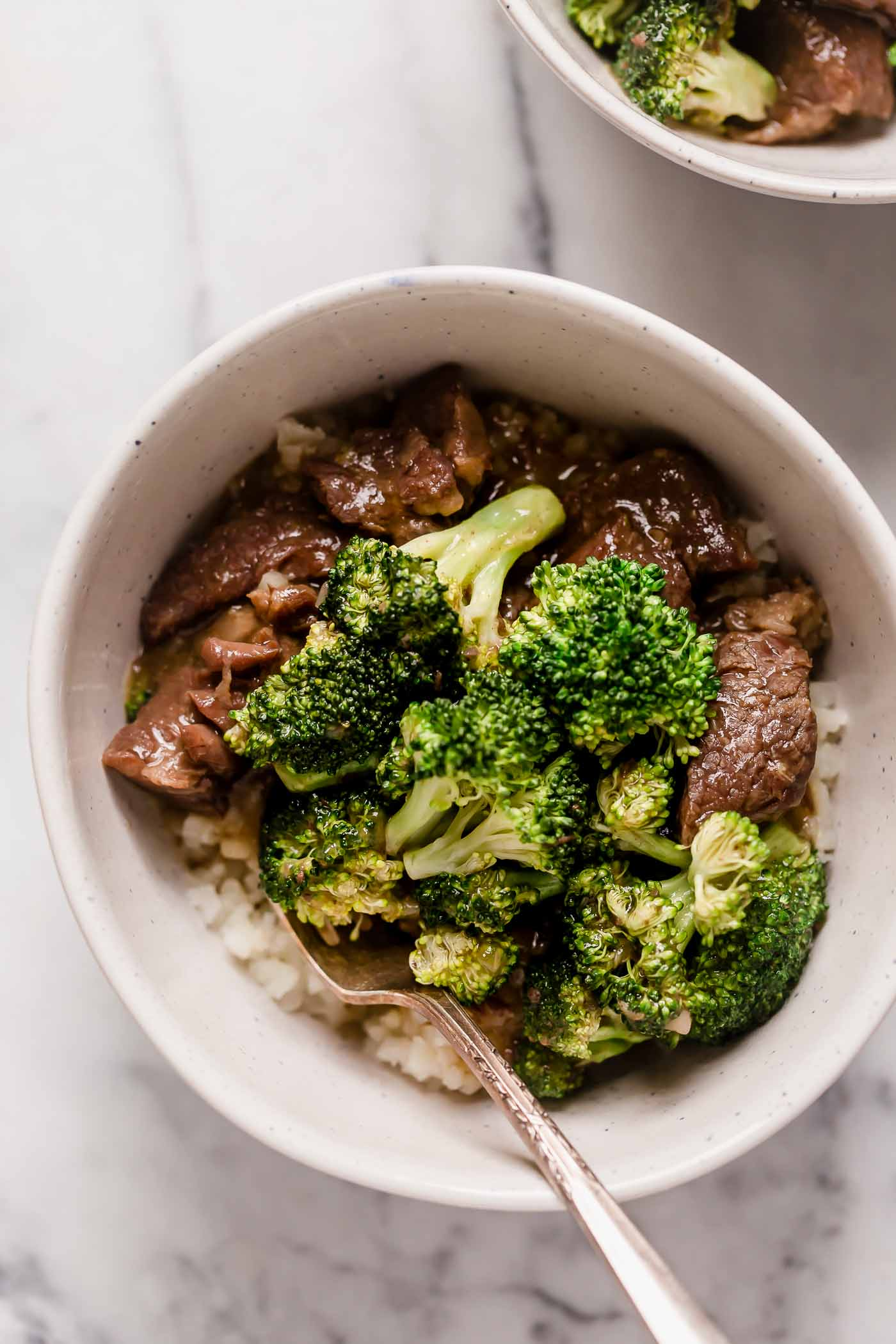 instant pot beef broccoli and rice in a ceramic bowl with a spoon