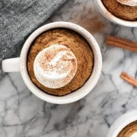 keto pumpkin pie mug cake with whipped cream and cinnamon on a marble table